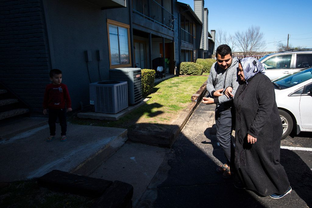 Abduljalil Jawish walks his mother Kadria Kharzoum to the apartment he shares with his brother, sister-in-law and their children on Wednesday.