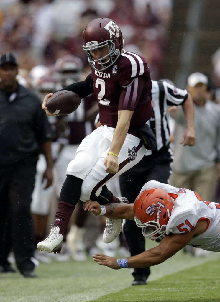 Texas A&M quarterback Johnny Manziel (2) leaps as Sam Houston State linebacker Eric Fieilo (51) hits him out of bounds during the first quarter of an NCAA college football game Saturday, Sept. 7, 2013, in College Station.