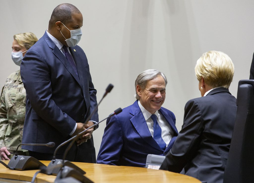 Governor Greg Abbott speaks to to Dallas Mayor Eric Johnson (left) and Fort Worth Mayor Betsy Price (right) following a press conference on Tuesday, June 2, 2020 at City Hall in Dallas.