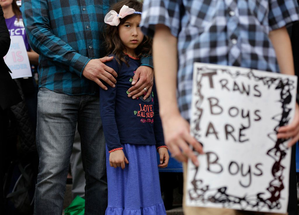 "Libby Gonzales stands with her father, Frank Gonzales, as she joins other members of the transgender community during a rally on the steps of the Texas Capitol, Monday, March 6, 2017, in Austin, Texas. The group is opposing a ""bathroom bill"" that would require people to use public bathrooms and restrooms that correspond with the sex on their birth certificate."