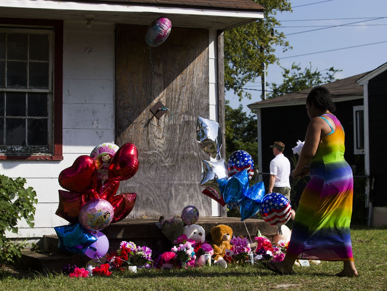 Adrian Moseley of Dallas plants a flower at a memorial as balloons and flowers wave in the wind at a home in the 2200 block of East Kiest Boulevard where a missing Lancaster teenager and a man were found dead early Sunday.