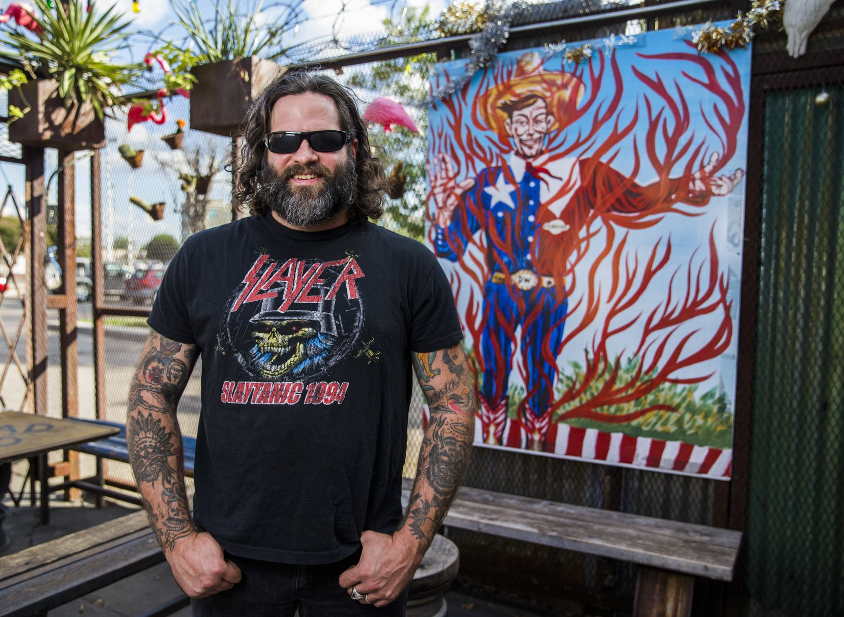 Artist Clay Stinnett with a print of his original flame-themed Big Tex painting at Double Wide bar in Dallas.