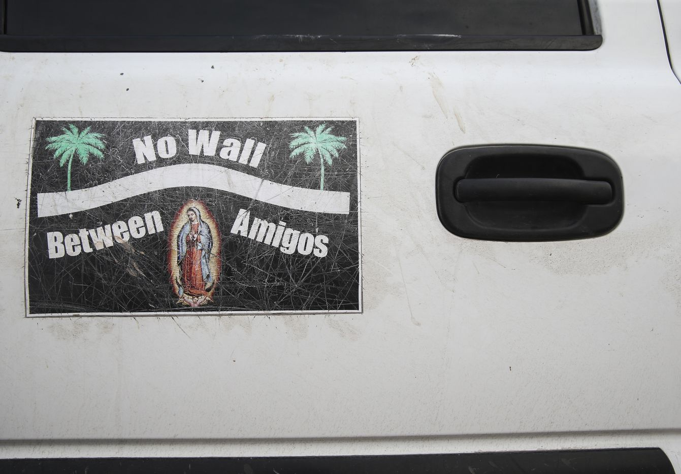 Door magnets and bumper stickers protesting the construction of a border wall adorn a white Chevy Suburban driven by Father Roy Snipes.