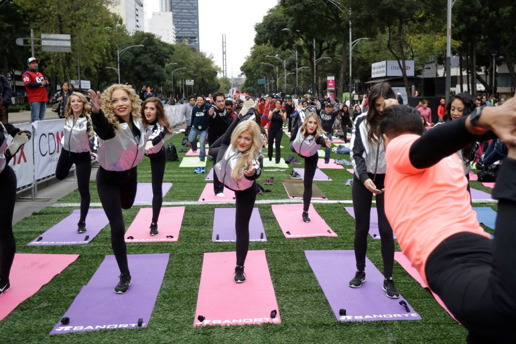 Oakland Raiders and Houston Texans cheerleaders took part in a yoga class in front of the Angel of Independence monument Sunday in Mexico City. The Texans play the Raiders tonight. (Gregory Bull/The Associated Press)