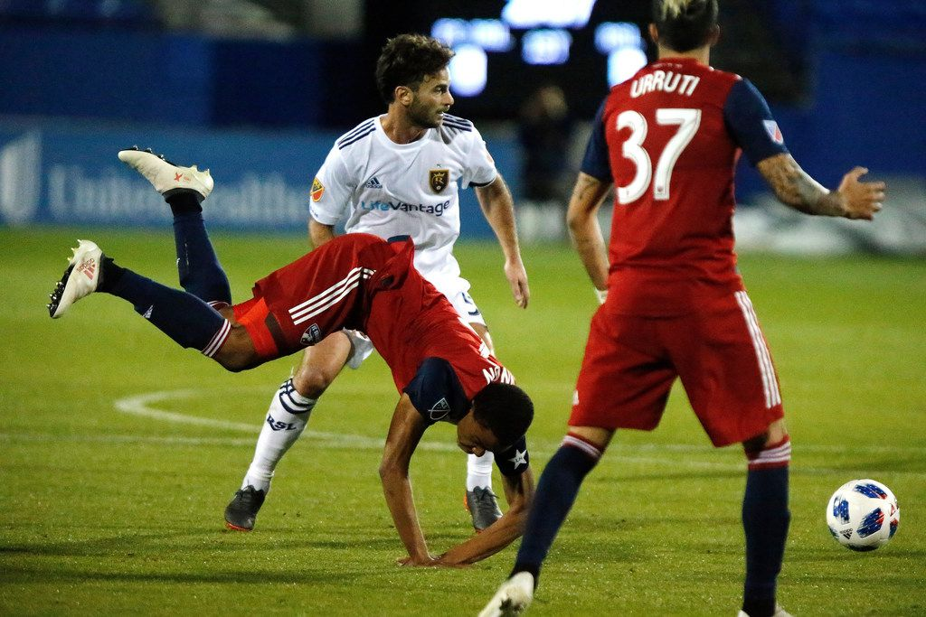 FC Dallas defender Reggie Cannon (2) goes down in front of Real Salt Lake midfielder Kyle Beckerman (5) as FC Dallas forward Maximiliano Urruti (37) looks on during the first half of an MLS soccer game in Frisco, Texas, Saturday, March 3, 2018. (Stewart F. House/The Dallas Morning News via AP)