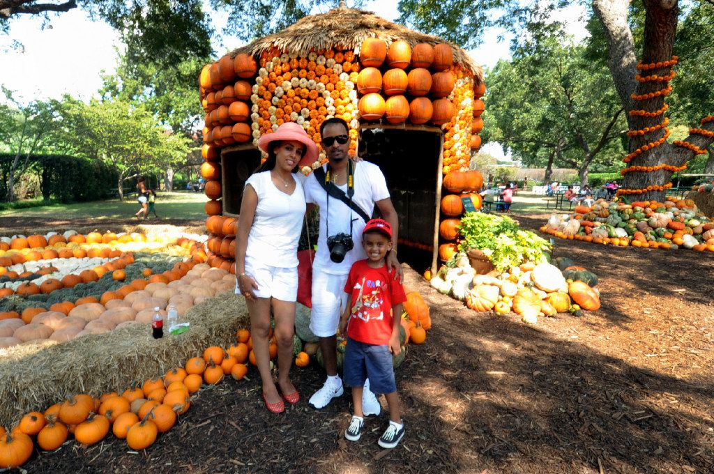 A family poses for a photo in the Pumpkin Village at the Dallas Arboretum and Botanical Garden.