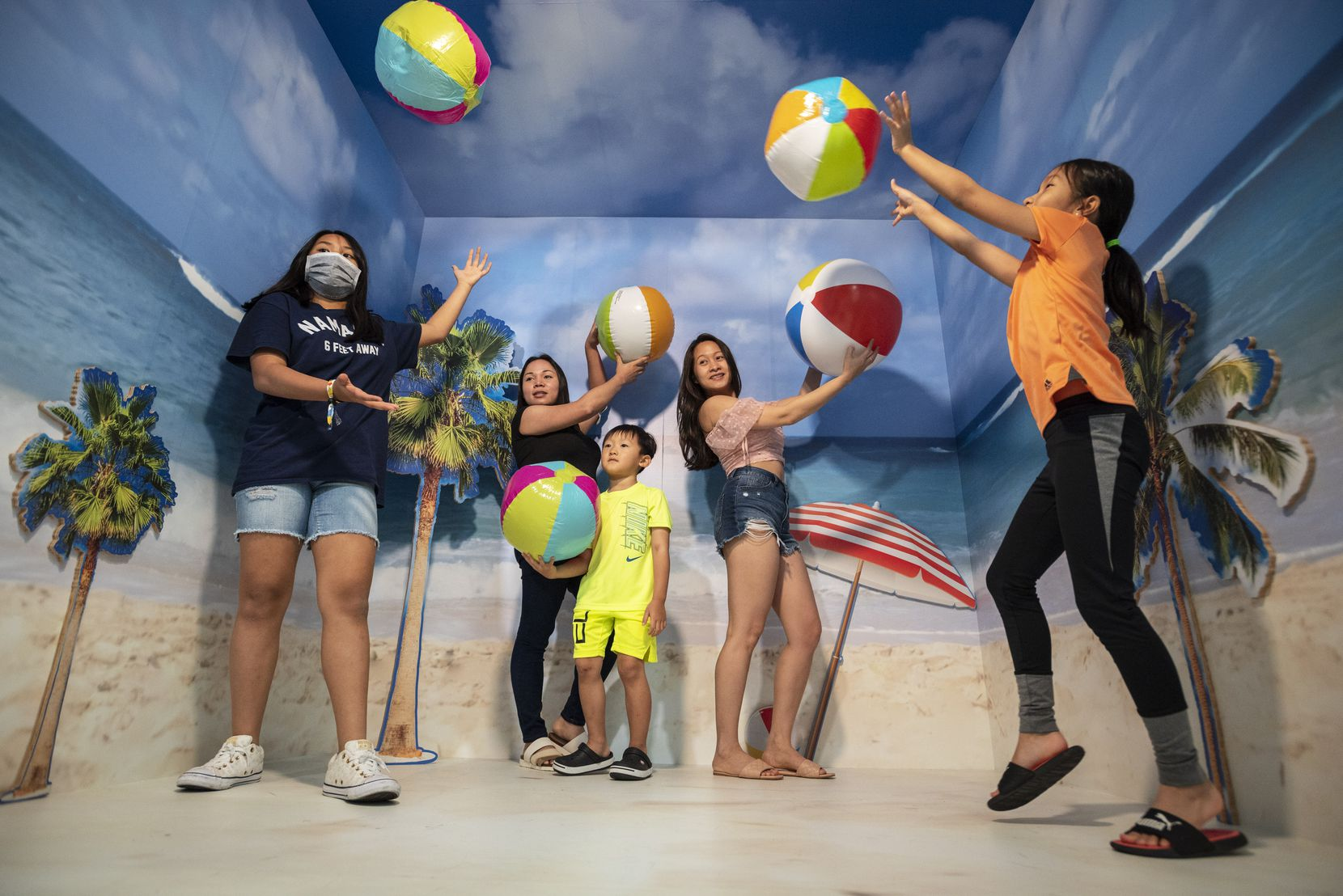 Hoan Le (center left) and Kelsy Duong (center right) take pictures with family members in one of the many vibrant settings at Pop! by Snowday, an immersive photo experience at Galleria Dallas. Beach balls are among a handful of provided props, and you can also take your own.