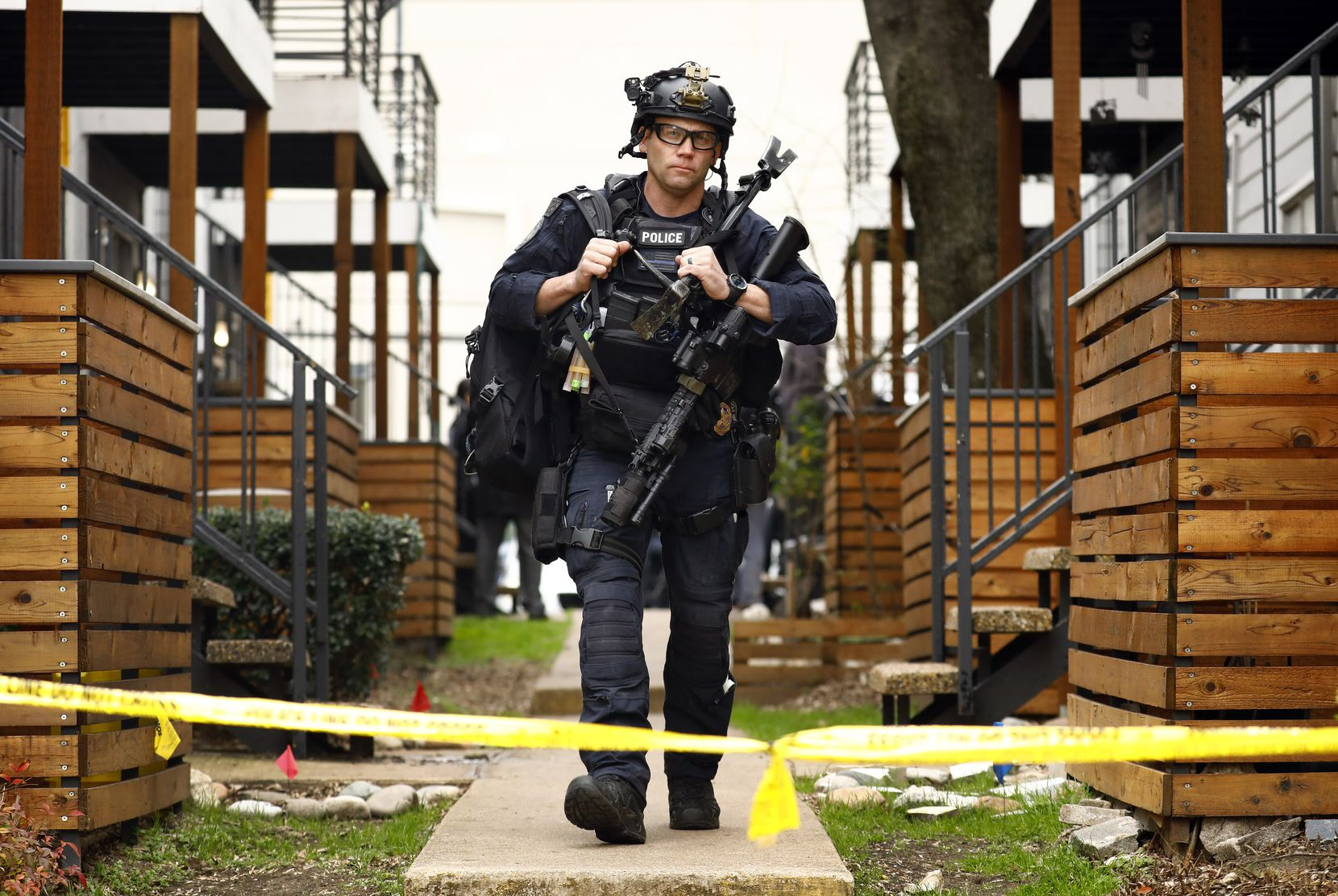 A SWAT officer leaves the scene where two children whose mother was found dead in their Far East Dallas apartment were found safe.