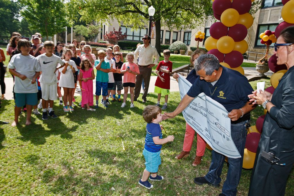 Jesus Gonzalez, a janitor for University Park Elementary School, is approached by Carson Caple, 1, after receiving a check for over $50,000 after having to relocate because his house is on campus at University Park Elementary School and is being torn down in Dallas on May 18, 2017.