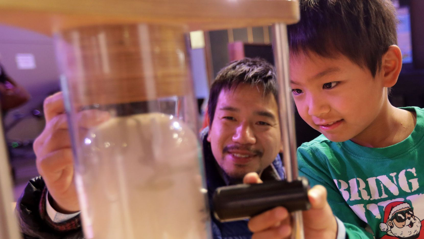 Takamichi Ono, left, and 6-year-old Masato Ono enjoy Sci-Tech Discovery Center in Frisco.