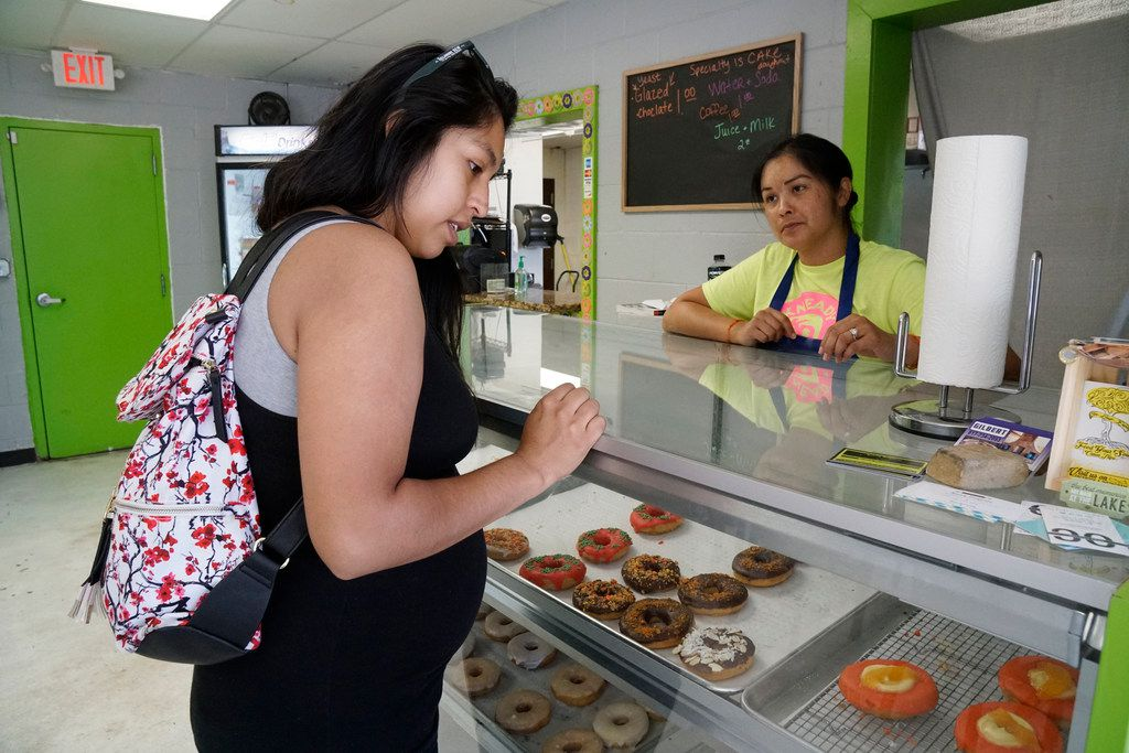 Alondra Barrera is assisted by Kneady Doughnuts co-owner Delilah Oudomsouk.