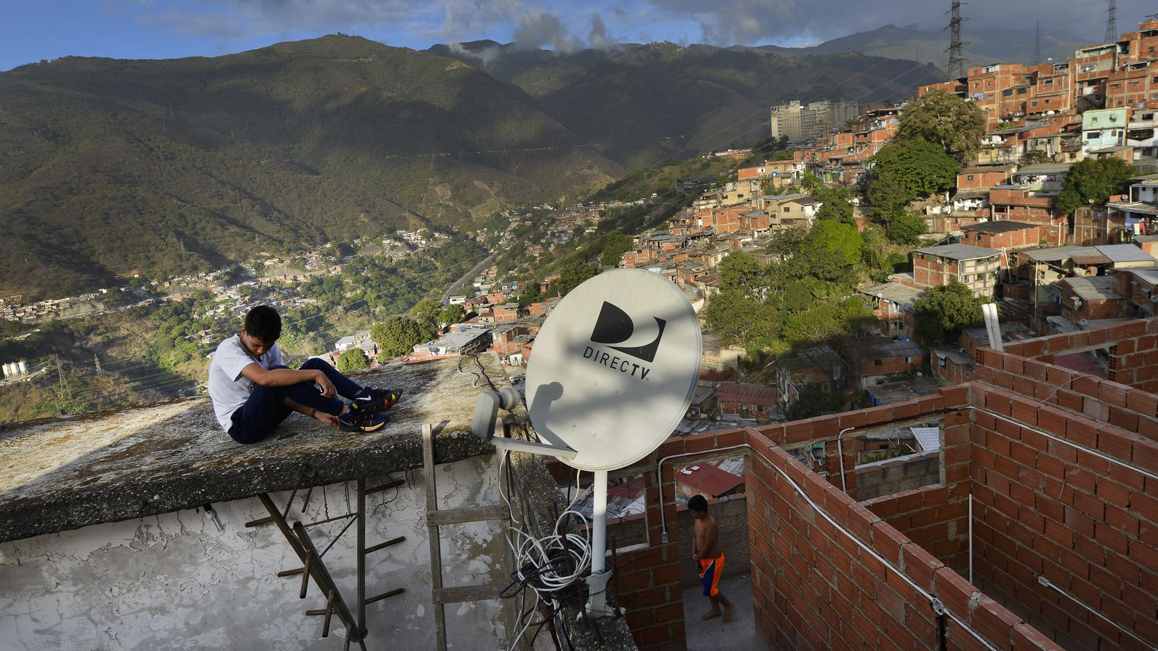 A DirectTV dish stands on home in the Catia neighborhood of Caracas, Venezuela, Thursday, Jan. 9, 2020. Venezuelan President Maduro's opponents want AT&T's DirecTV unit to restore a number of channels it was required to take down from its lineup.