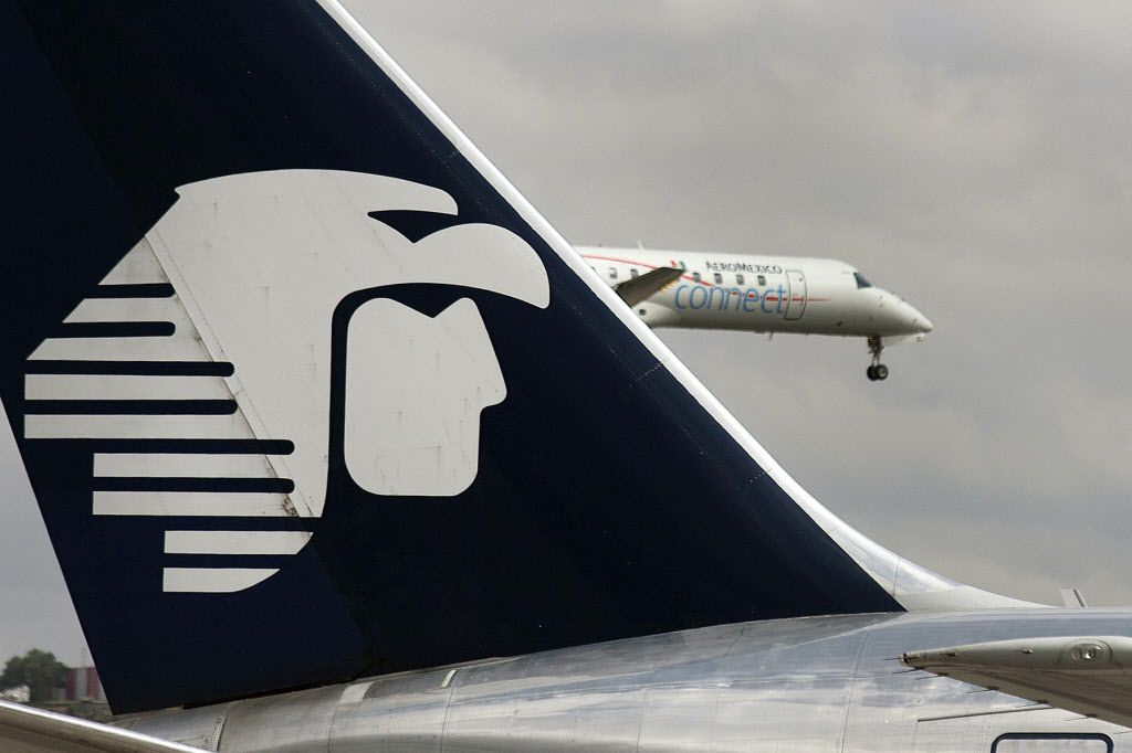 The Grupo Aeromexico SAB logo is seen on the tail of a plane as another jet takes off from Benito Juarez International Airport in Mexico City, Mexico, on Monday, Sept. 10, 2012.