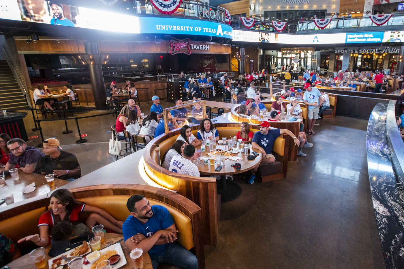 Fans eat and gather during opening day of the Texas Rangers season at Texas Live! in Arlington, Texas, on Friday, July 24, 2020. The Rangers played the Colorado Rockies at the new Globe Life Field stadium, but fans had to watch on televised screens outside due to the ongoing pandemic. (Lynda M. Gonzalez/The Dallas Morning News)