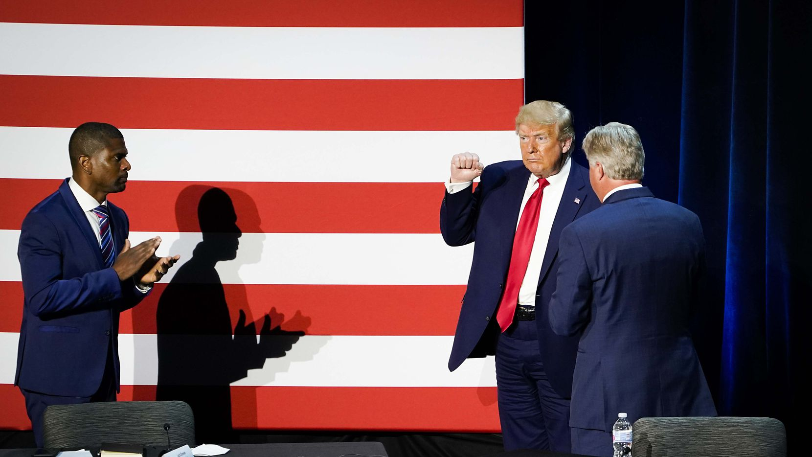 Jack Brewer (left) applauds as President Donald Trump acknowledges the crowd at the conclusion of a roundtable conversation about race relations and policing at Gateway Church Dallas Campus on Thursday, June 11, 2020, in Dallas.
