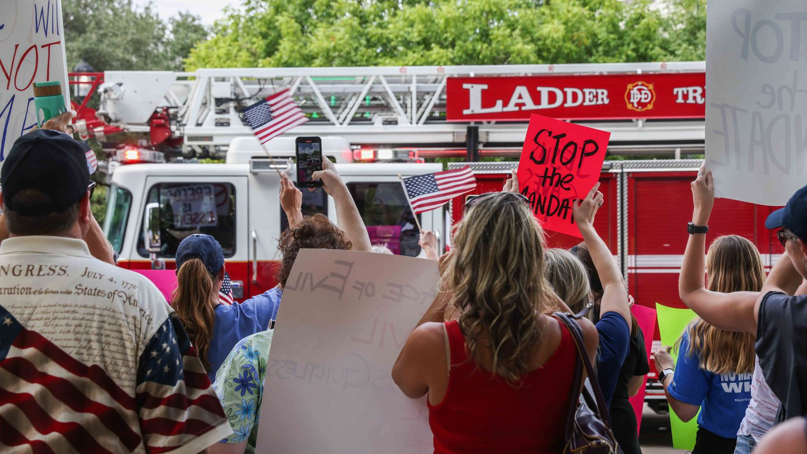 Firefighters in a Dallas fire truck drive through the street as they honk their horn, drawing cheers from the crowd while protesting on COVID-19 vaccine mandates at Baylor University Medical Center on Saturday, August 7, 2021. (Lola Gomez/The Dallas Morning News)