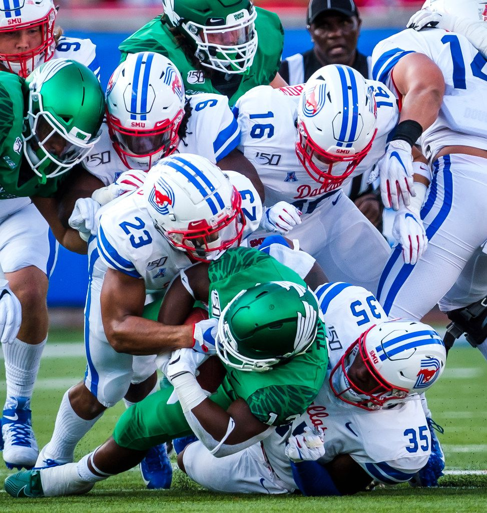 UNT running back DeAndre Torrey (13) is brought down by SMU safety Rodney Clemons (23), defensive end Delontae Scott (35) and safety Trevor Denbow (16) during the first half of an NCAA football game at Ford Stadium on Saturday, Sept. 7, 2019, in Dallas. (Smiley N. Pool/The Dallas Morning News)