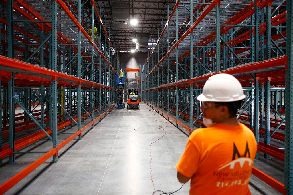 Construction workers build shelving at the new North Texas Food Bank in Plano.