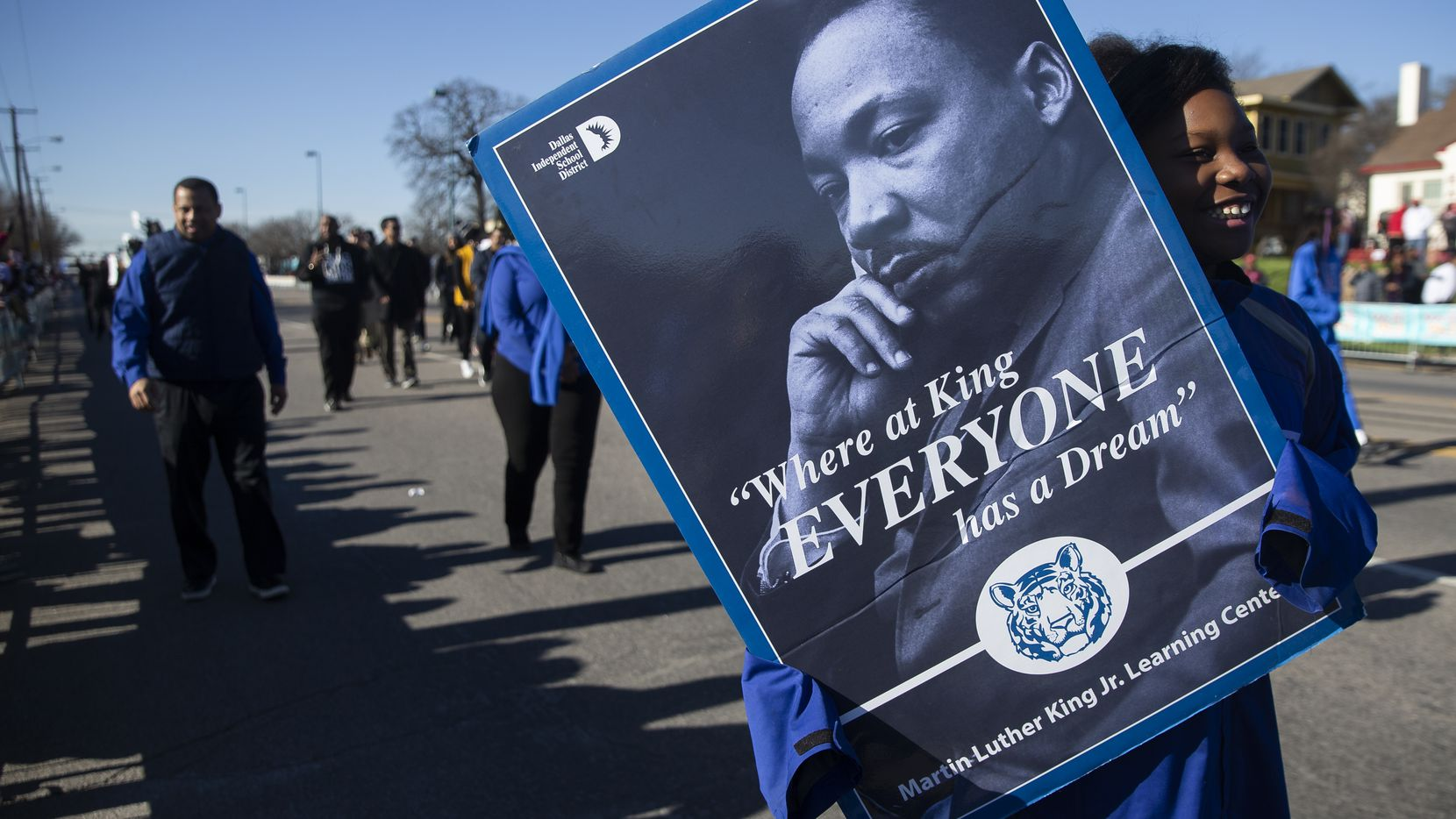 A student with the Martin Luther King JR. Learning Center holds a photo of MLK in the 38th annual MLK Parade on Jan. 20, 2020 in Dallas.