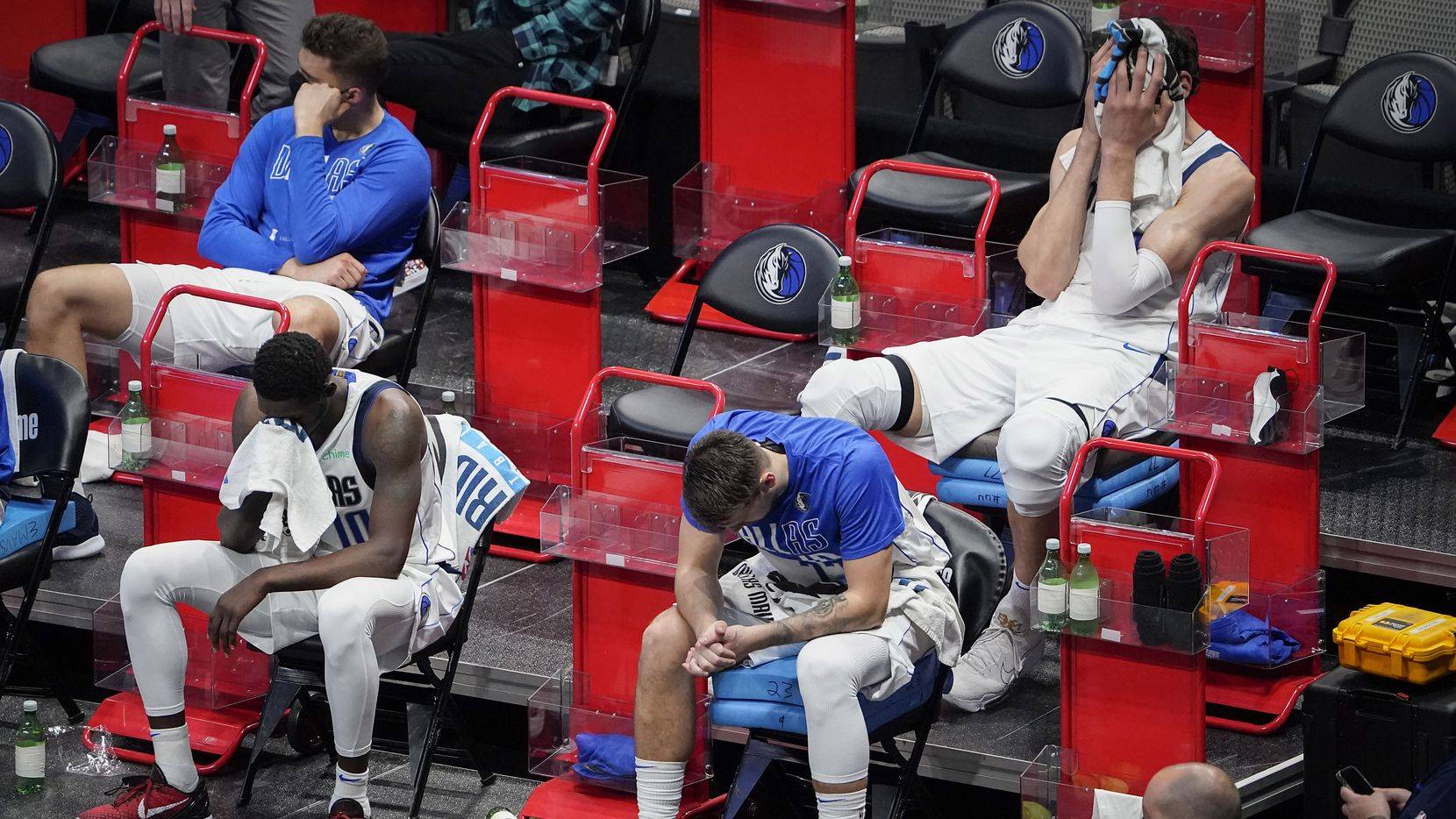 Dallas Mavericks guard Luka Doncic sits (bottom right) on the bench with forward Dorian Finney-Smith (bottom left), forward Maxi Kleber (top left) and center Boban Marjanovic (top right) during the fourth quarter of a loss to the LA Clippers in an NBA playoff basketball game  at American Airlines Center on Sunday, May 30, 2021, in Dallas.  The Clippers won the game 106-81.