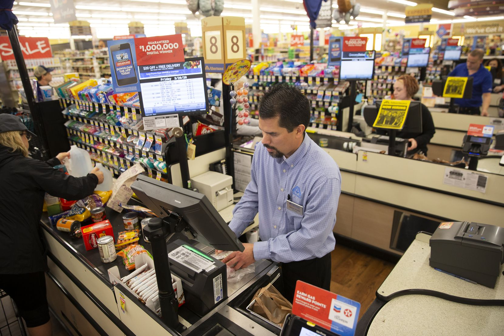 Shaun Paeth, head of general merchandise, jumps on the register at Albertson's on March 20, 2020 in Colleyville. Paeth said that it wasn't normal for the store to be this busy on an early Friday morning before the new coronavirus outbreak. (Juan Figueroa/ The Dallas Morning News)