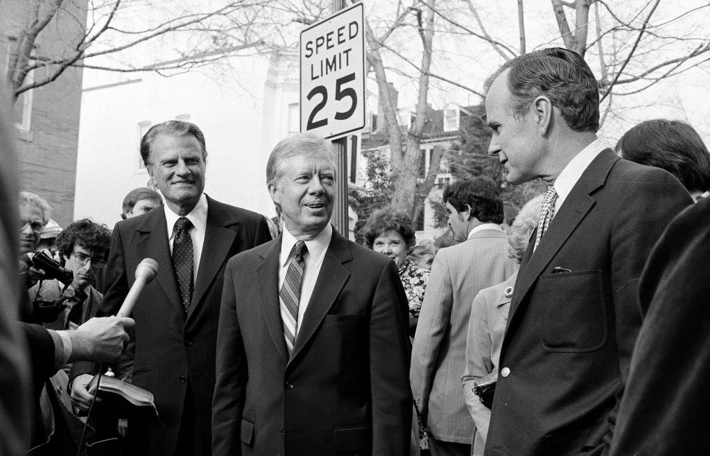 President Jimmy Carter answers a reporter's question outside the Georgetown Baptist Church in Washington, Dec. 7, 1980, where the Rev. Billy Graham held services.  Vice President-elect George Bush, right, is seen at right.
