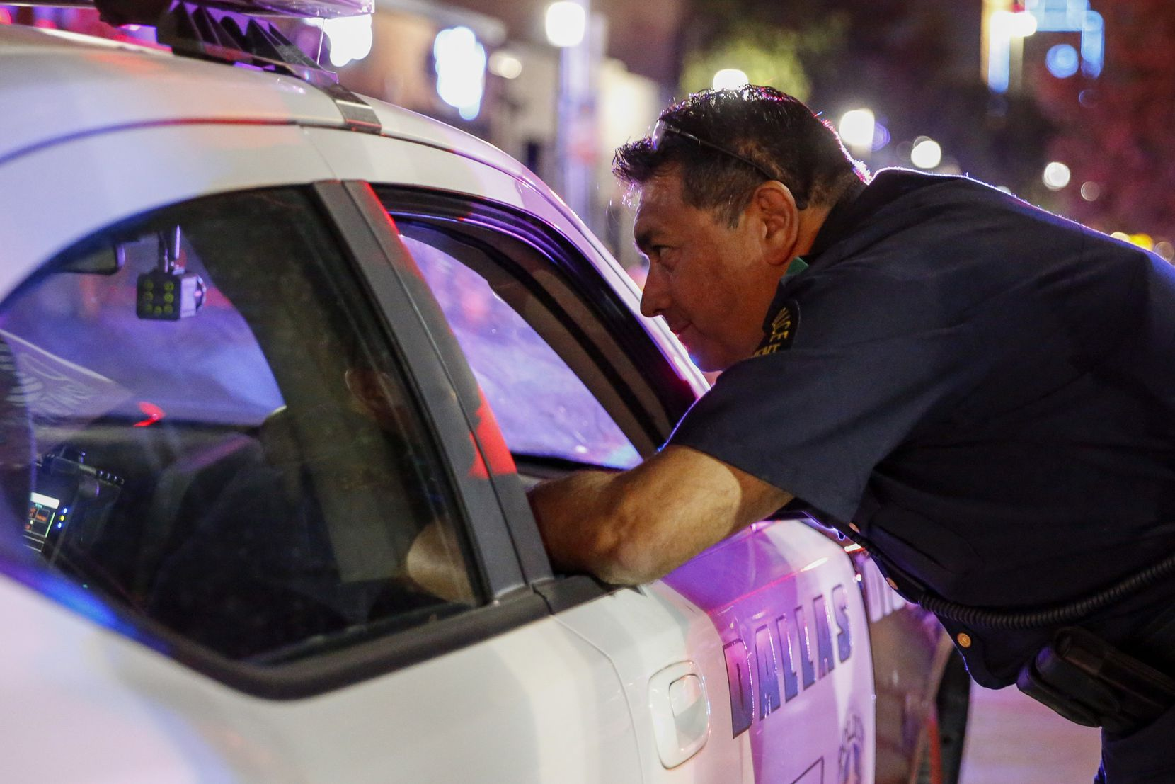 Herrera visits with another officer while on patrol in Dallas' Deep Ellum entertainment district, just east of downtown.