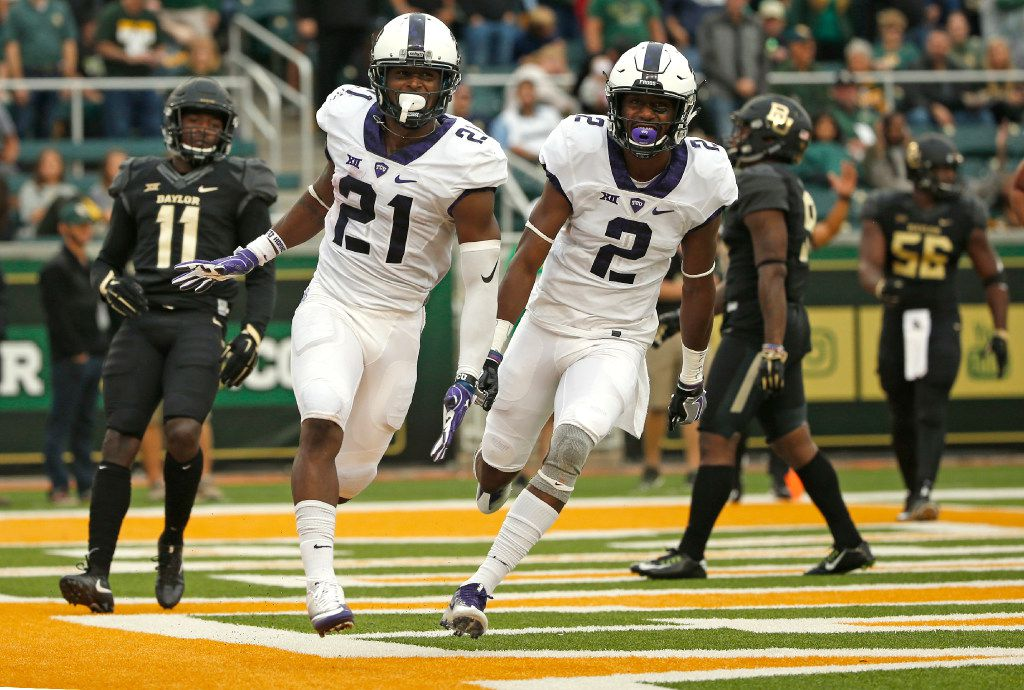 WACO, TX - NOVEMBER 5:  Kyle Hicks #21 of the TCU Horned Frogs celebrates with teammate Desmon White #10 as Jameson Houston #11 of the Baylor Bears looks on after Hicks scored on a touchdown run against the Baylor Bears in the first half at McLane Stadium on November 5, 2016 in Waco, Texas. (Photo by Ron Jenkins/Getty Images)