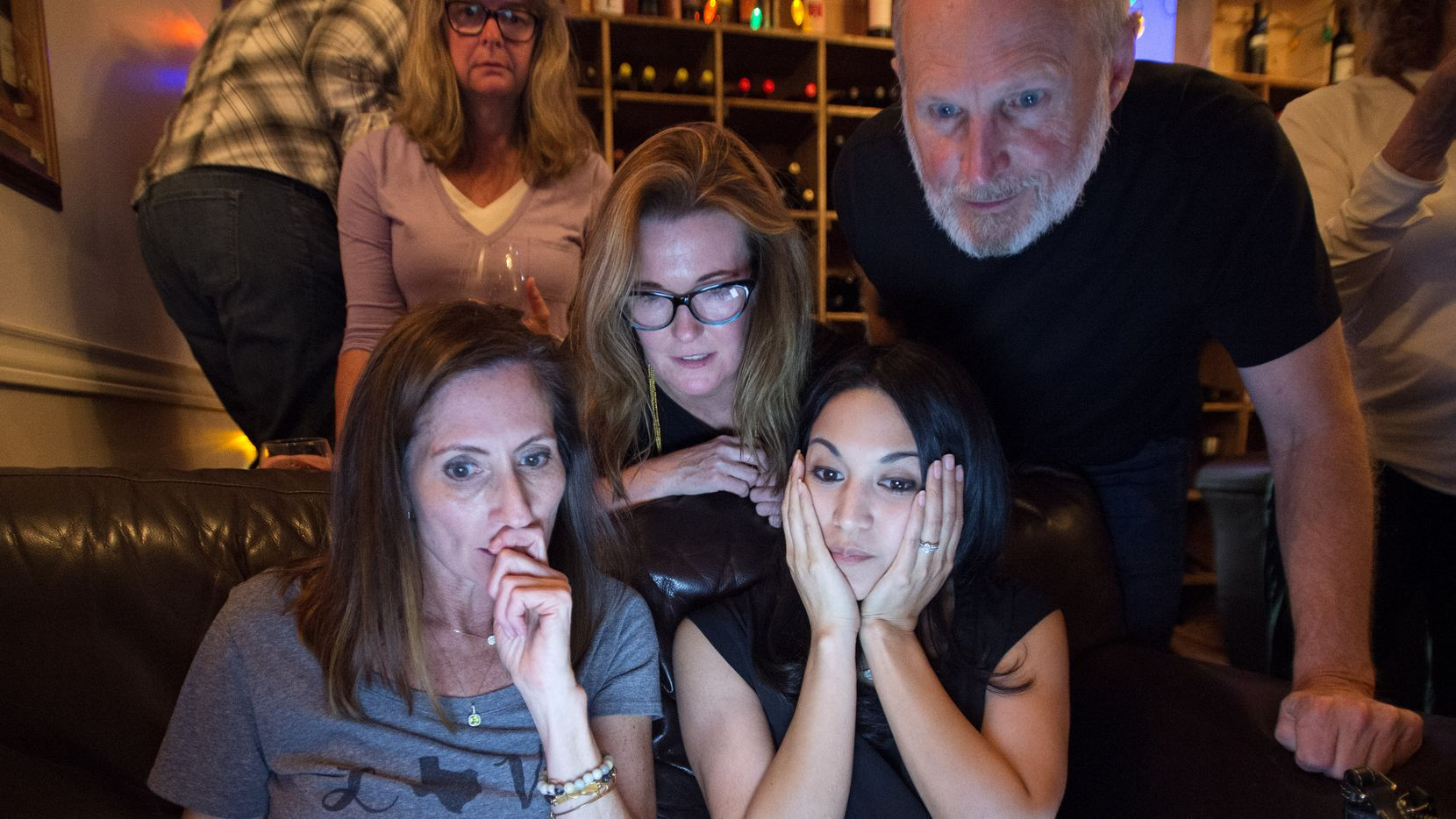 Dallas ISD District 2 board of trustee candidate Lori Kirkpatrick (front left), campaign volunteer Diana Carranza, (front right), campaign manager Trish Watson (center, behind couch), and campaign volunteer Tom Ervin monitor election results at a watch party Saturday, May 6, 2017 at Bodega Wine Bar in Dallas.