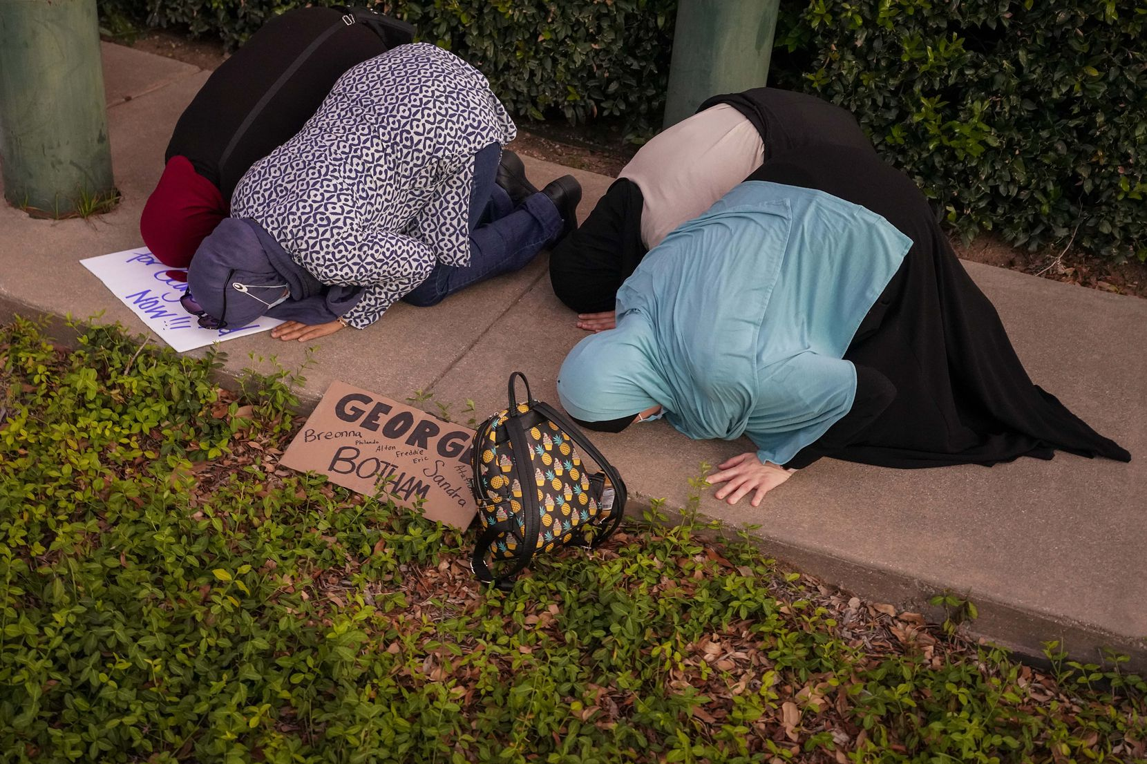 A group of muslim women steps aside from the crowd and puts down their protest signs to kneel in prayer during a rally against police brutality at the Dallas Police Headquarters on Friday, May 29, 2020, in Dallas.
