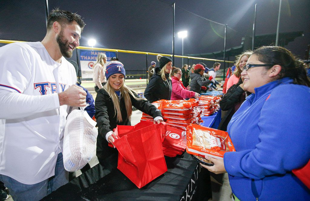 Texas Rangers Joey Gallo bags a frozen turkey for Erica Cortez, right, at the Texas Rangers MLB Youth Academy at Mercy Street Sports Complex in Dallas, Friday, November 22, 2019. The Texas Rangers Baseball Foundation donated turkeys, sides, and desserts to nearly 200 families for the Thanksgiving holiday.