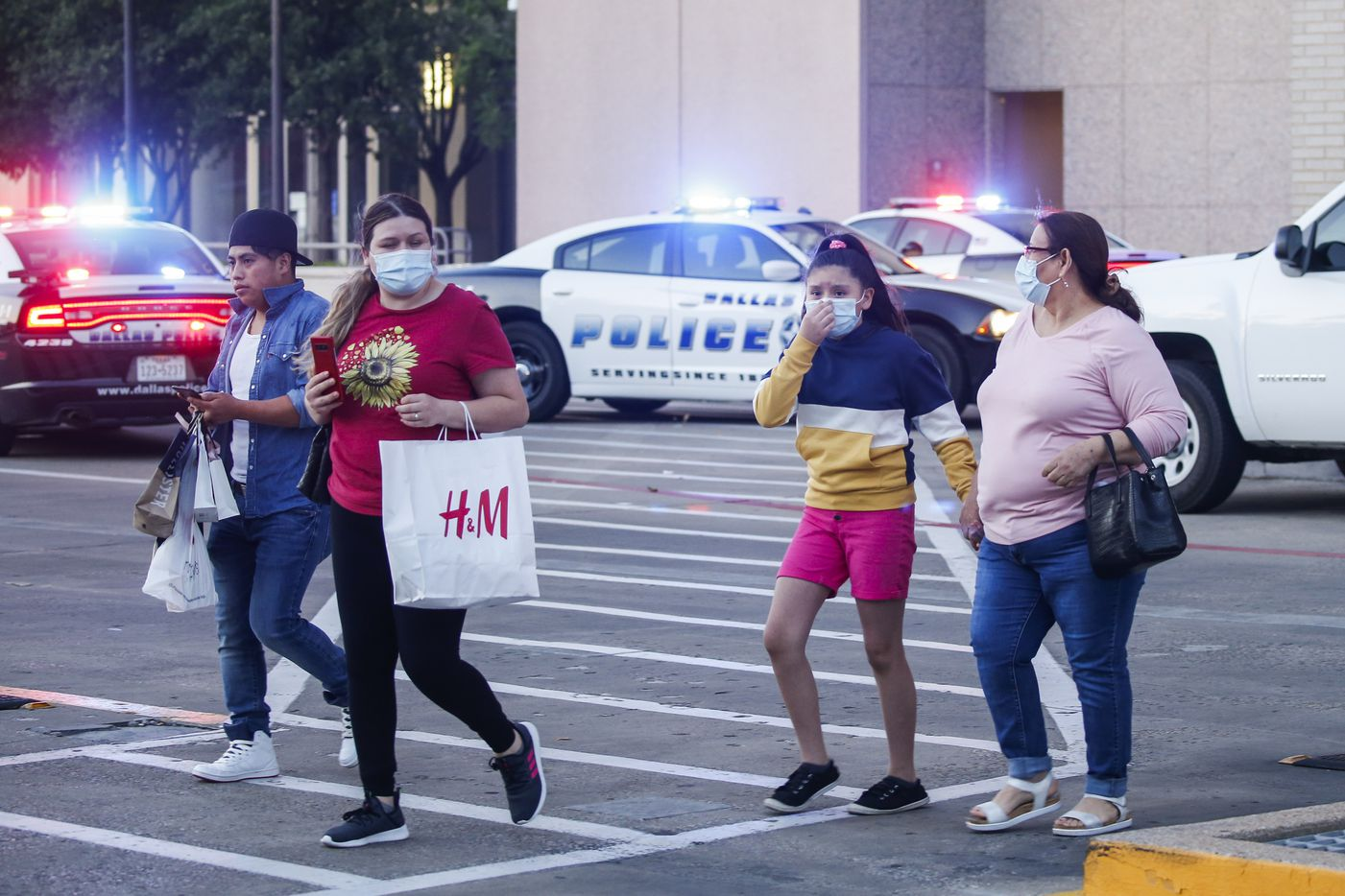 People are escorted out of Galleria Dallas mall, where a shooting was reported Tuesday, June 16, 2020 in Dallas.