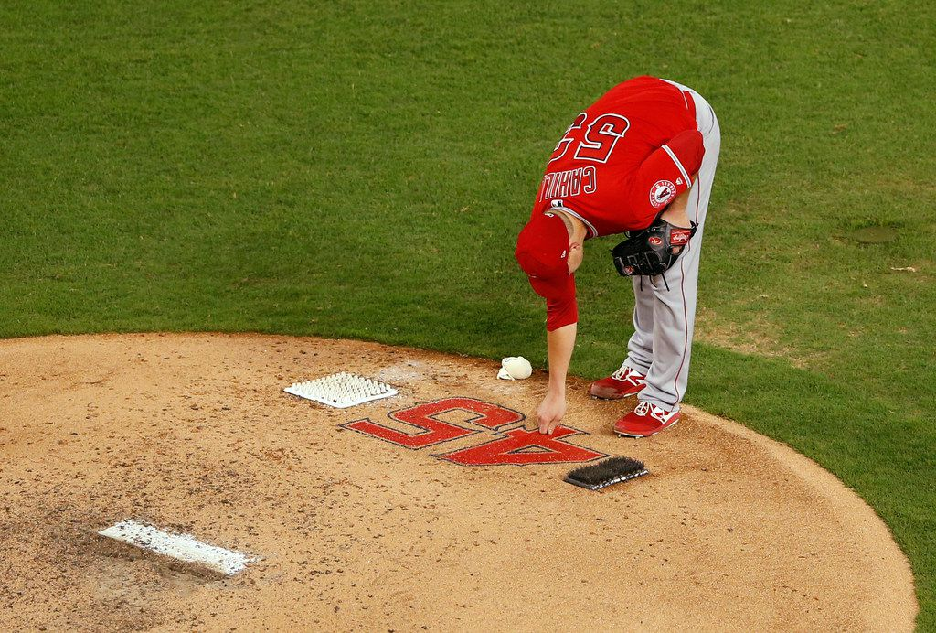 Los Angeles Angels pitcher Trevor Cahill (53) touches the number of Los Angeles Angels Tyler Skaggs (45) at the mound before pitching against the Texas Rangers during the fifth inning of play at Globe Life Park in Arlington, Texas on Tuesday, July 2, 2019. Los Angeles Angels Tyler Skaggs was found dead in his Southlake hotel room prior to the scheduled game against the Texas Rangers.
