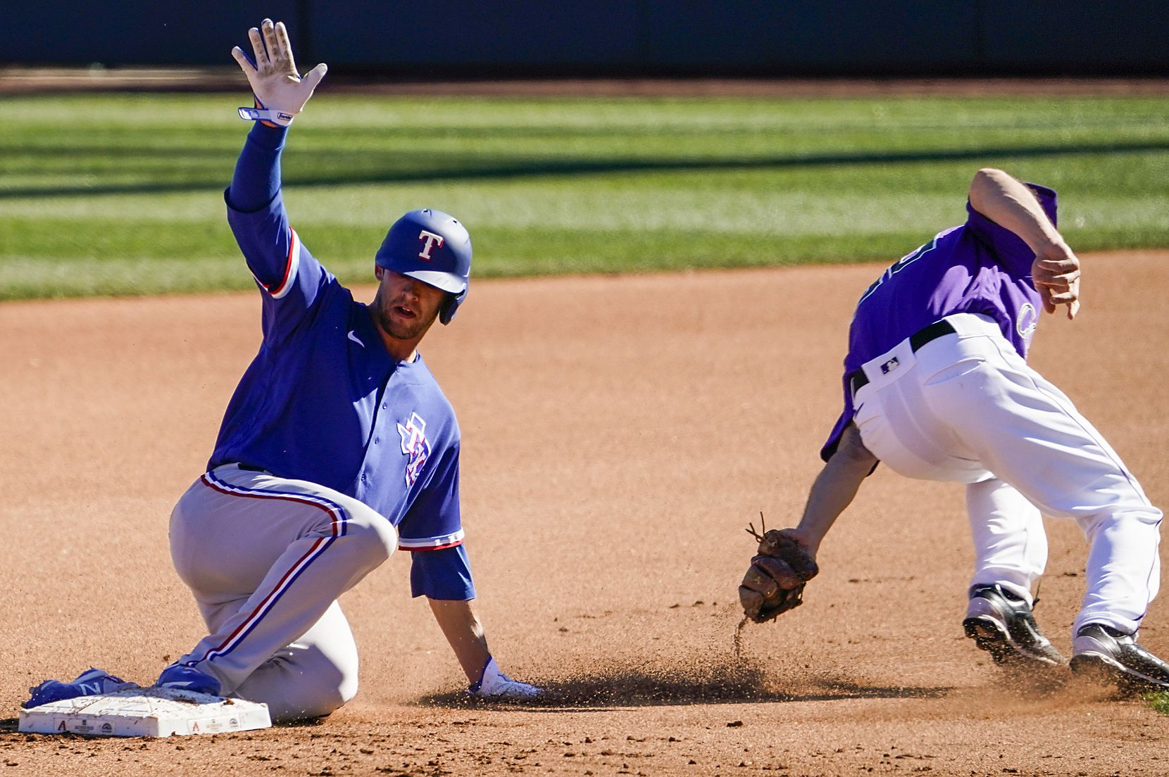 Texas Rangers infielder Eli White slides past the tag of Colorado Rockies second baseman Kelby Tomlinson to steal second base during the seventh inning of a spring training game at Salt River Fields at Talking Stick on Wednesday, Feb. 26, 2020, in Scottsdale, Ariz.