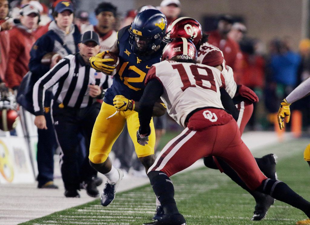 West Virginia wide receiver Gary Jennings Jr. (12) Is forced out of bounds by Oklahoma linebacker Curtis Bolton (18) and defensive back Brendan Radley-Hiles (44) during the first half of an NCAA college football game Friday, Nov. 23, 2018, in Morgantown, W.Va. (AP Photo/Raymond Thompson)