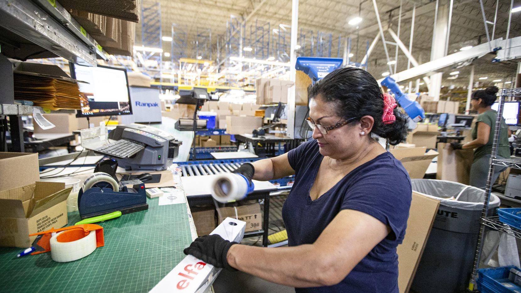 Carmen Hernandez prepares merchandise for shipping at The Container Store's distribution center in Coppell.