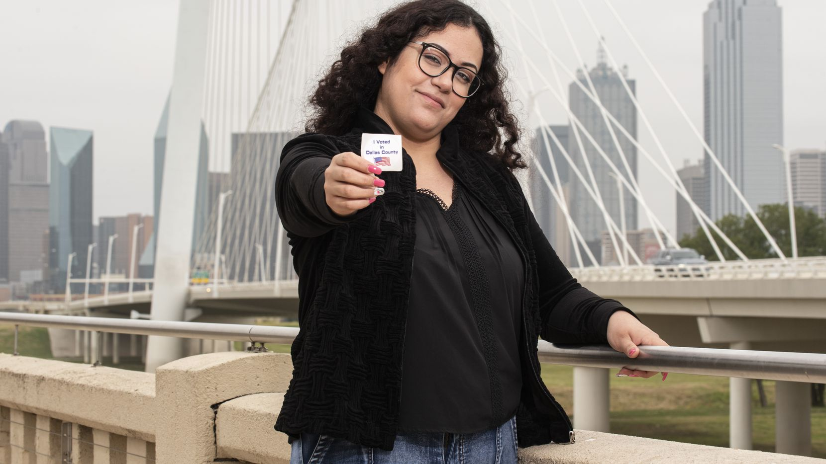 "First time voter Ana Rubalcava, 24, of Irving, holds her ""I voted in Dallas County"" sticker after she voted for the first time, on Monday, Oct. 19, 2020 photographed at the Ronald Kirk Pedestrian Bridge in Dallas."