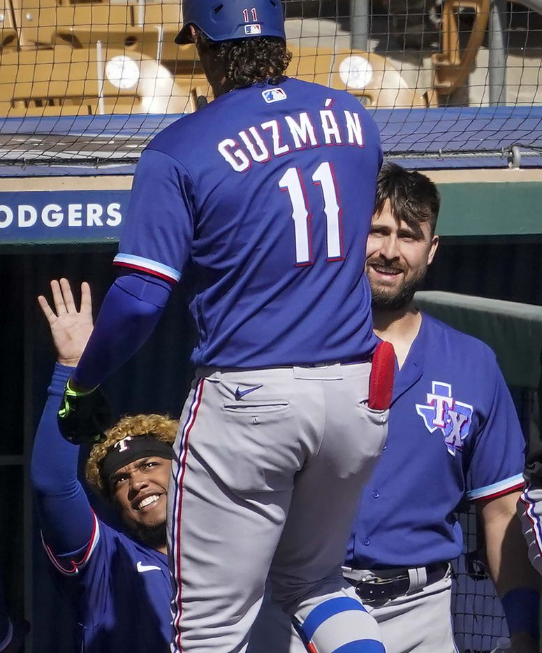 Texas Rangers first baseman Ronald Guzmán (11) gets a hand from left fielder Willie Calhoun (left) and right fielder Joey Gallo after hitting a solo home run during the second inning of a spring training game at Camelback Ranch on Tuesday, March 2, 2021, in Phoenix, Ariz.