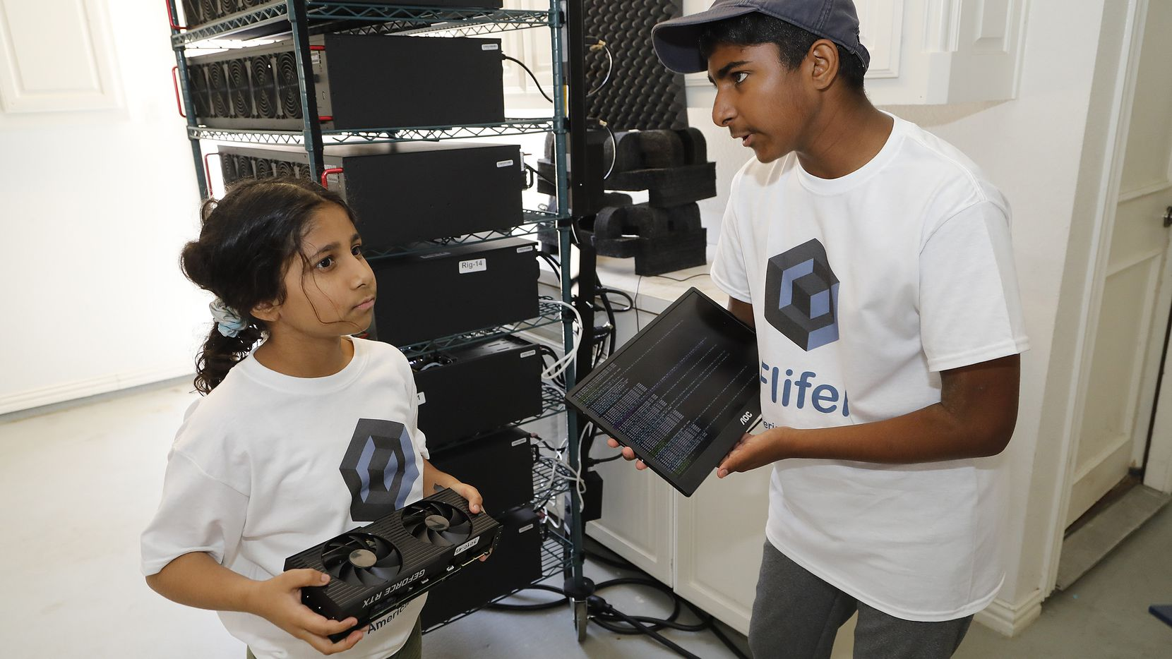Frisco residents Aanya Thakur, 9, and her brother Ishaan, 14, discuss the computer equipment they use to mine cryptocurrency out of their garage.