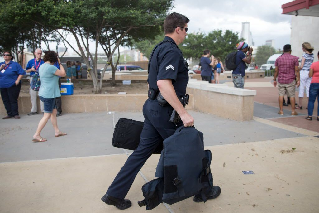 A DPD police officers carry heavy armor and rifle bag into the Dallas Police Headquarters on July 9, 2016 in Dallas. (Ting Shen/The Dallas Morning News)