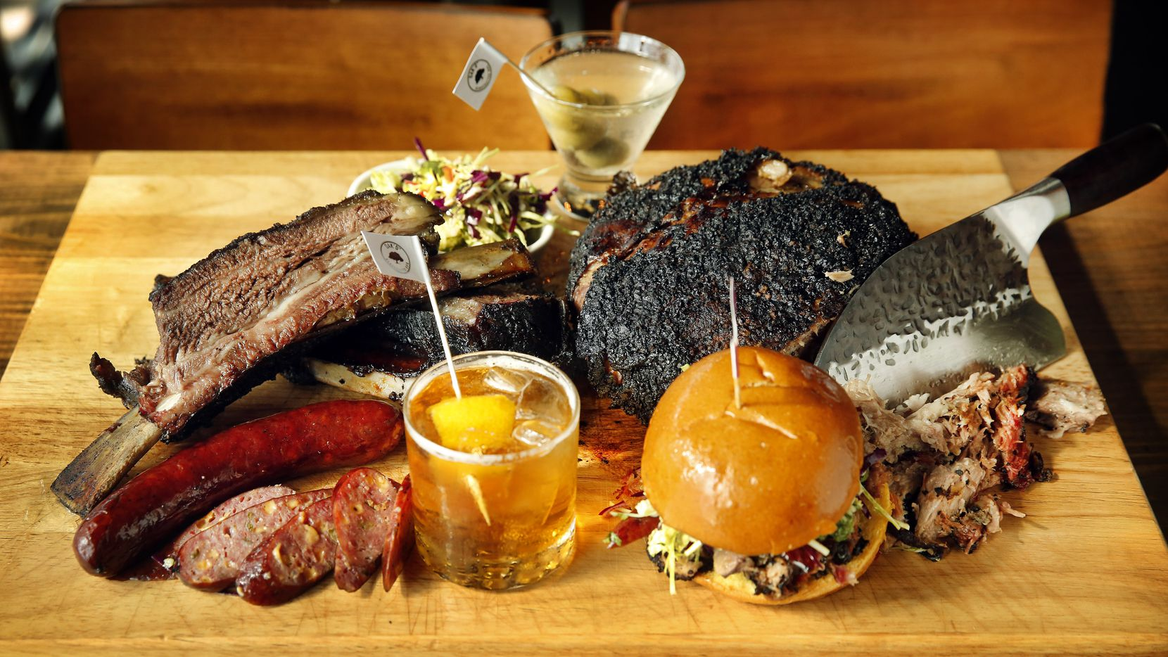 Oak'd opened Nov. 6, 2020. The menu includes beef ribs, jalapeño cheddar sausage, A Sandwich and Some Lovin' (named for celebrity radio host Kellie Rasberry's podcast), and chopped pork butt. Also pictured are two signature cocktails named for the radio host and her husband Allen Evans.