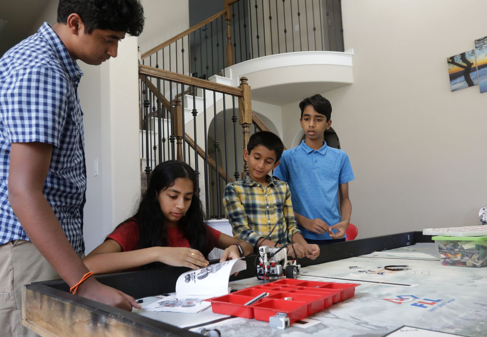 Mihit Sai Garlanka (from left) assists 13-year-old Samriddhi Garlanka, 11-year-old Santhosh Kavula and 12-year-old Jai Muppalla as they build a LEGO robot at his home in McKinney.