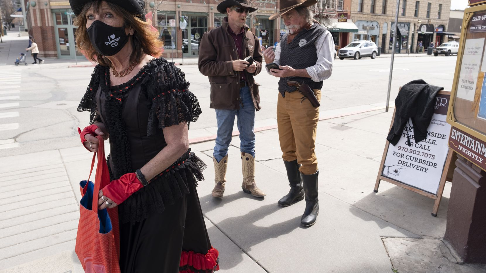 Dressed in Old West attire, Cathy Roberts (left) and Scott Perez (right) mix it up with locals and visitors while on a mission in Durango, Colo.: to encourage mask use during the pandemic. They give out free masks and sometimes stand for a quick photo opportunity with tourists.