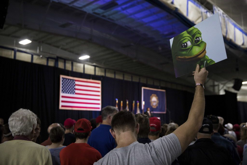An attendee at a Trump rally in New Hampshire holds a sign featuring Pepe the Frog, a cartoon tied to anti-Semitism and racism that has become an unofficial mascot of the alt-right.