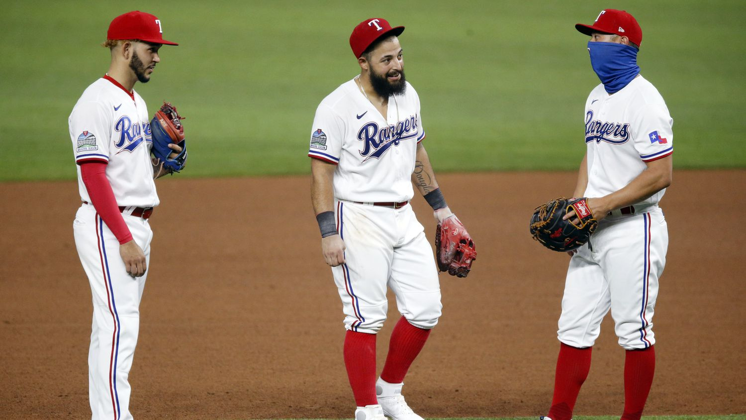 Texas Rangers second baseman Rougned Odor (center) visit with teammates Rob Refsnyder (right) and Anderson Tejada during a pitching change in the ninth inning against the Seattle Mariners at Globe Life Field in Arlington, Monday, August 10, 2020.