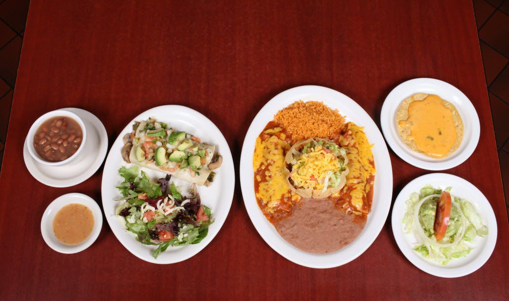 A spread by Ojeda's at 4617 Maple Ave. in Dallas. On the left is Naked Mushroom Enchiladas with sliced avocado, pico de gallo, salad and beans. On the right, Ojeda's Dinner - small guacamole salad, chile con queso on tostada, two beef enchiladas, 1 puffed taco, rice and refried beans.