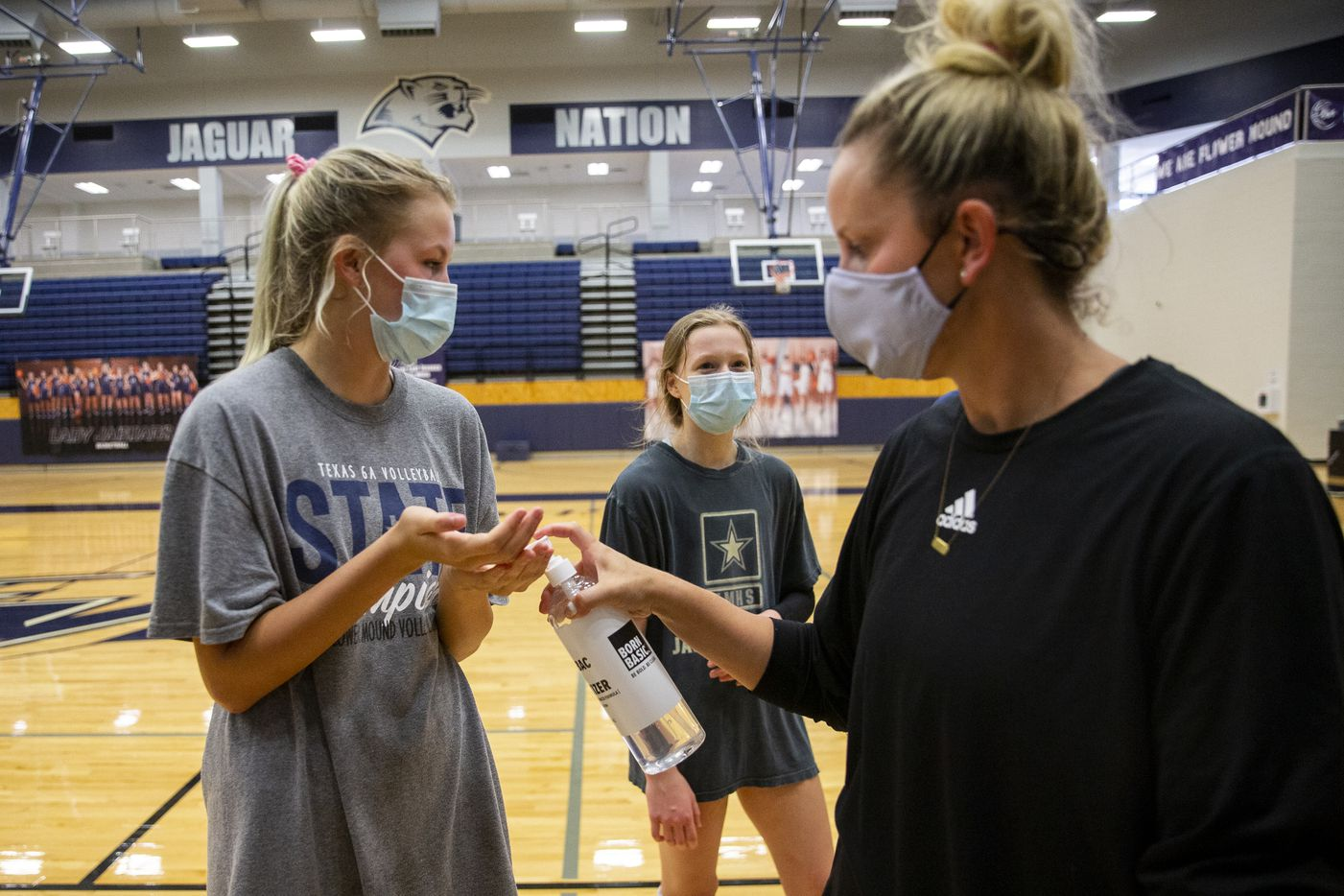 Flower Mound High School volleyball coach Jamie Siegel (right) gives player Gabby Walker hand sanitizer after practice on Sept. 8, 2020 in Flower Mound. (Juan Figueroa/ The Dallas Morning News)