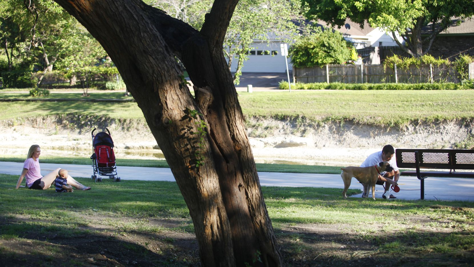 In this 2011 file photo, a family takes a break in the shade while walking the trail in a residential area that connects Huffhines Park with Duck Creek Linear Park in Richardson. This area is near where sidewalk construction will be occurring on Plano Road between Arapaho and Apollo roads.