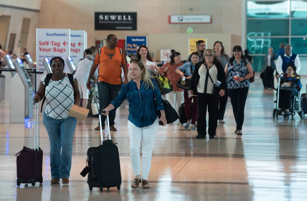 Airline passengers walk through the ticketing area as they walk to the security check-in at Dallas Love Field on Wednesday, May 23.
