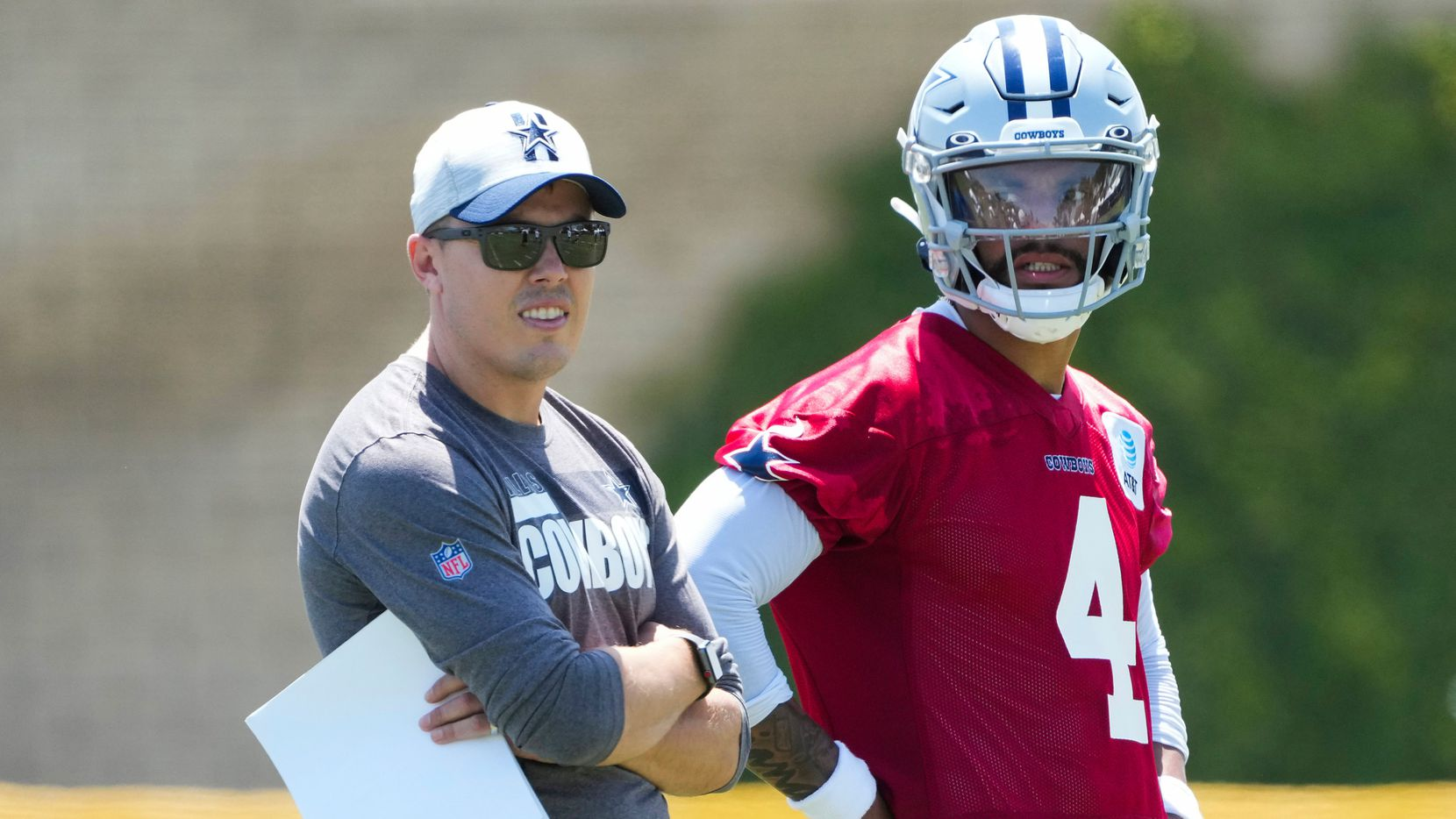 Dallas Cowboys quarterback Dak Prescott (4) talks with offensive coordinator Kellen Moore during the first practice of the team's training camp on Thursday, July 22, 2021, in Oxnard, Calif.